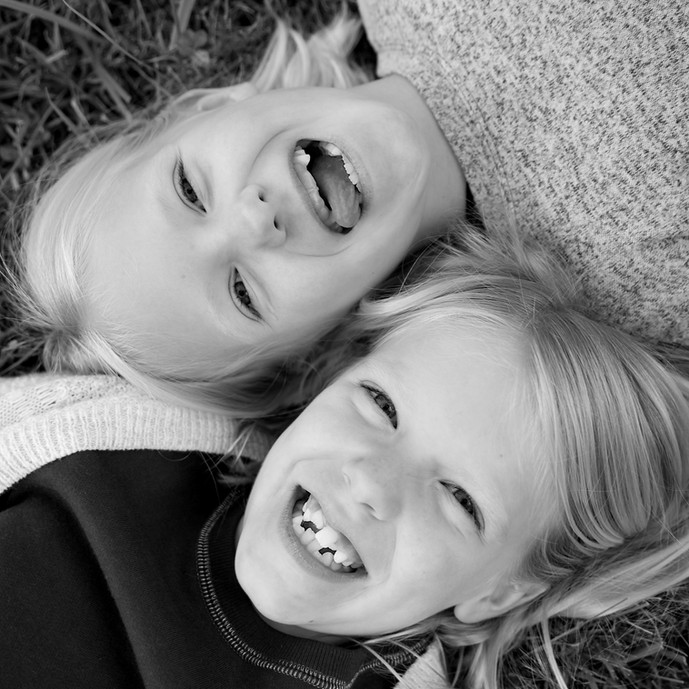 A black and white portrait of two girls laying on the ground.