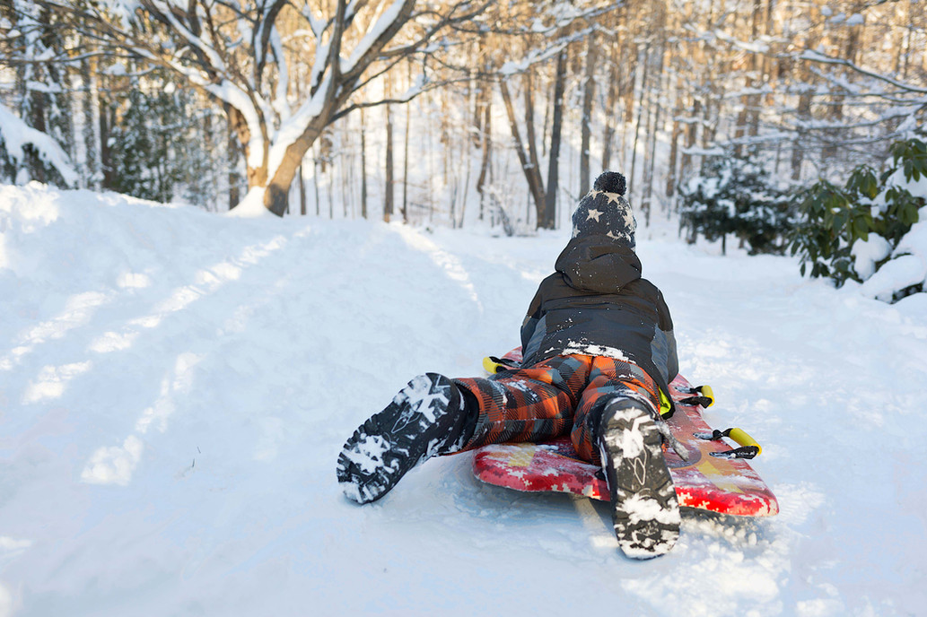 A boy on a sled at the top of a hill of snow.