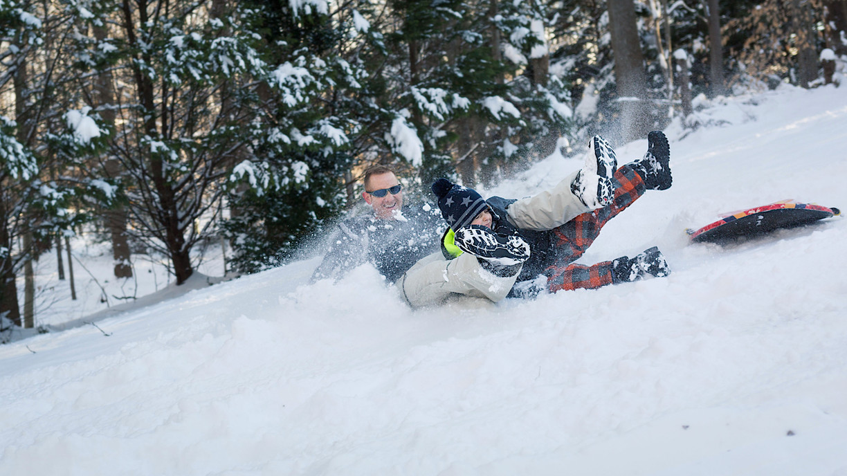 A dad and son sliding down a hill of snow.