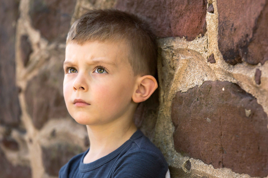 A portrait of a boy in front of a rock wall.