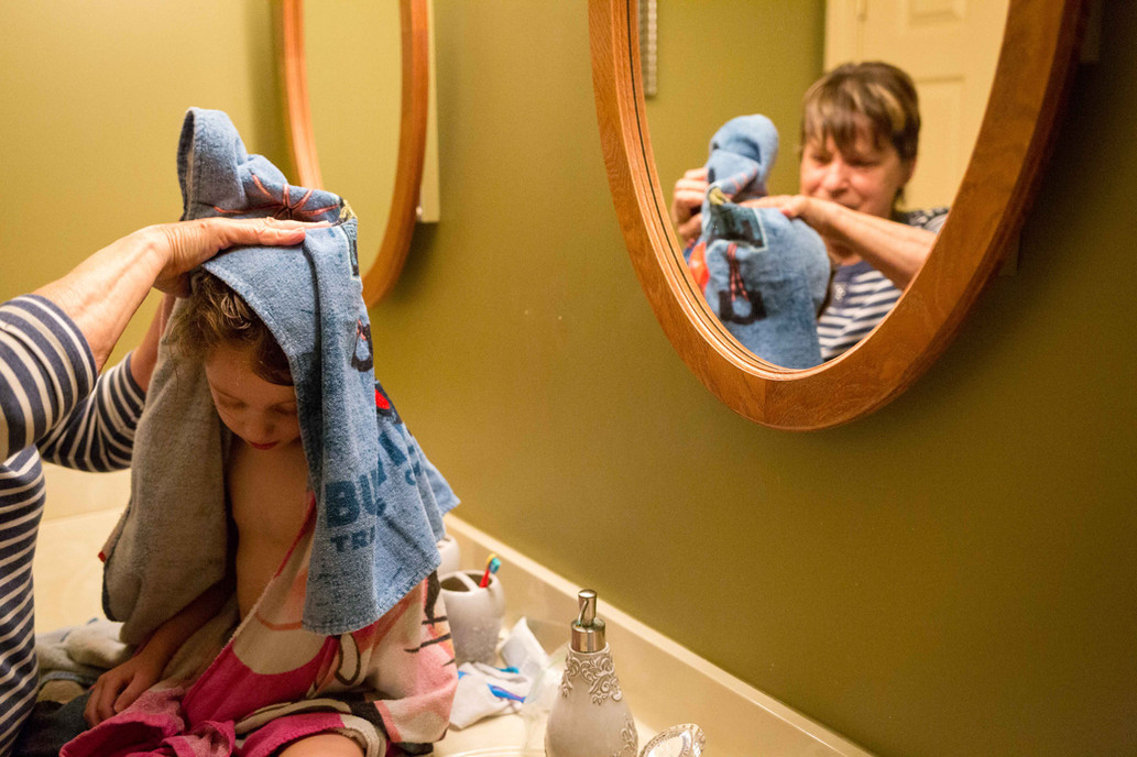 A young girl getting her hair dried after bath.