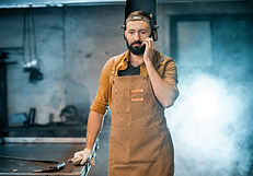 welder-with-phone-at-the-workshop-TSH7AD