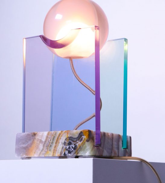 """Inspired by the Renaissance floor plans of the villas, the light bulb is erected by two plates in crystal resin, displaying a weightless balancing act. The three-dimensional effect of the resin, it's lightness and even the smell, brings me back to my childhood when I used to play with the objects that my grandfather created, but the use of raw materials have been part of my life too; my father is a geologist so he taught me the properties and characteristics of minerals. The Onyx has been used in prehispanic Mexico to create religious objects and jewelry, I like to use """"Mexican Onyx"""" because of its ancient use and the particular green nuances that makes it so unique."""