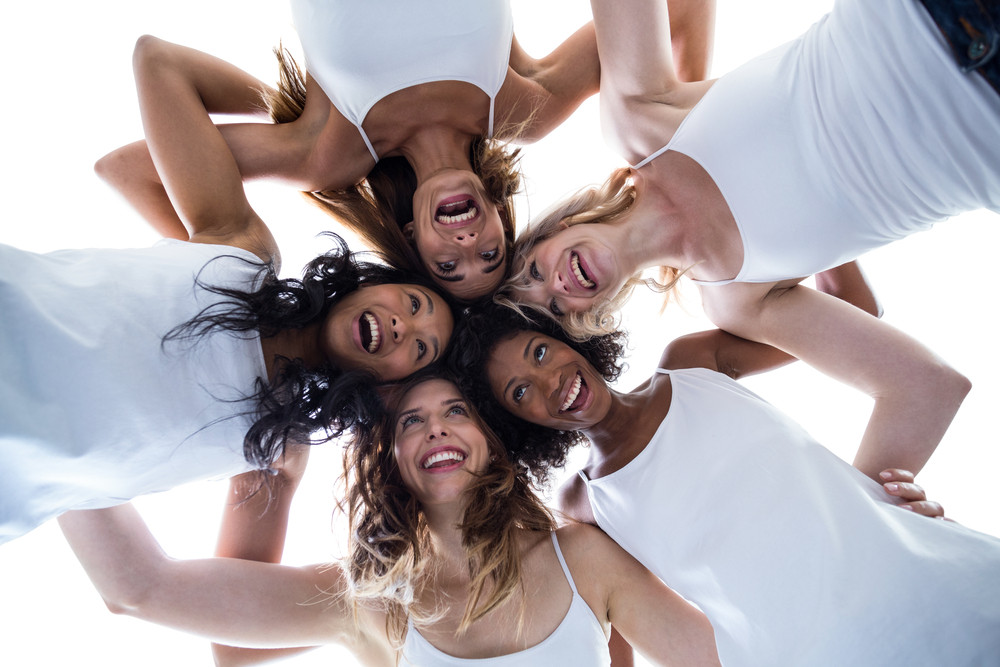 Five smiling women wearing white with their heads together in a circle configuration