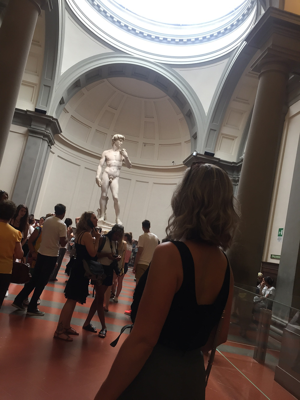 Woman pictured from the back looks down the hallway of the Accademia Gallery to the statue of David bathed in light