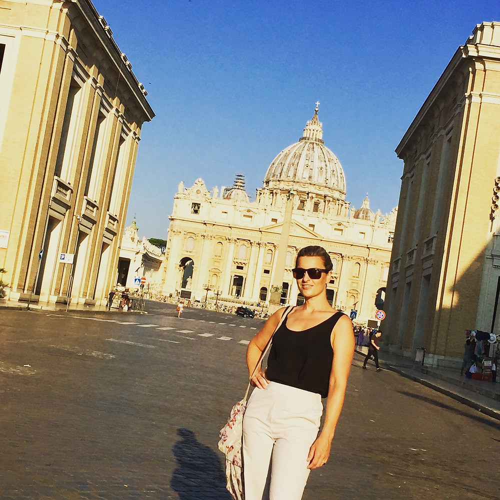Woman strikes a pose in front of St. Peter's Basilica in the Vatican City