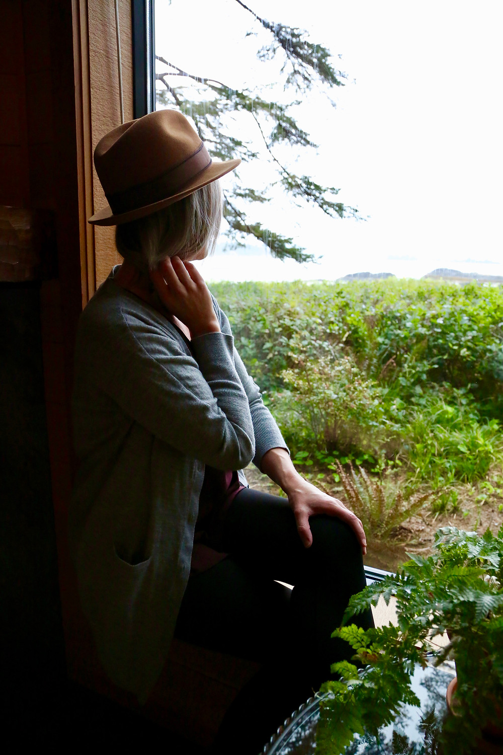 Woman sits by the window lookig out of her room at the Wickaninnish Inn at Chesterman beach in Tofino BC