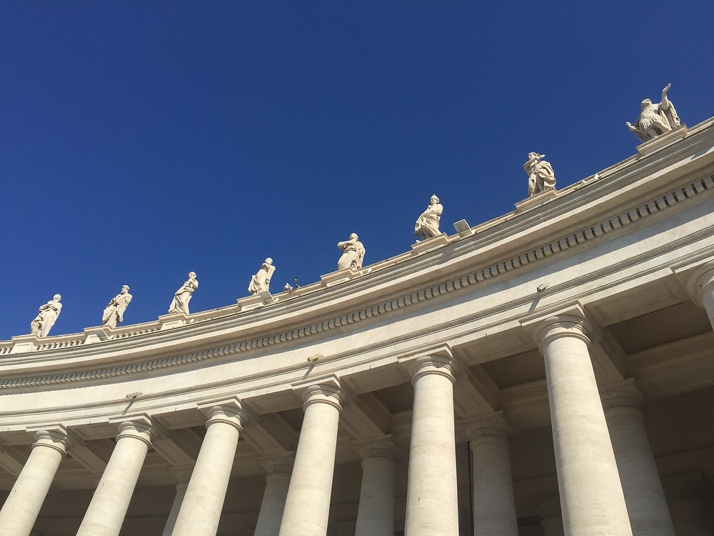 blue skies and bright sun bath the Saint Statues on the Colonnades of St Peter's Square