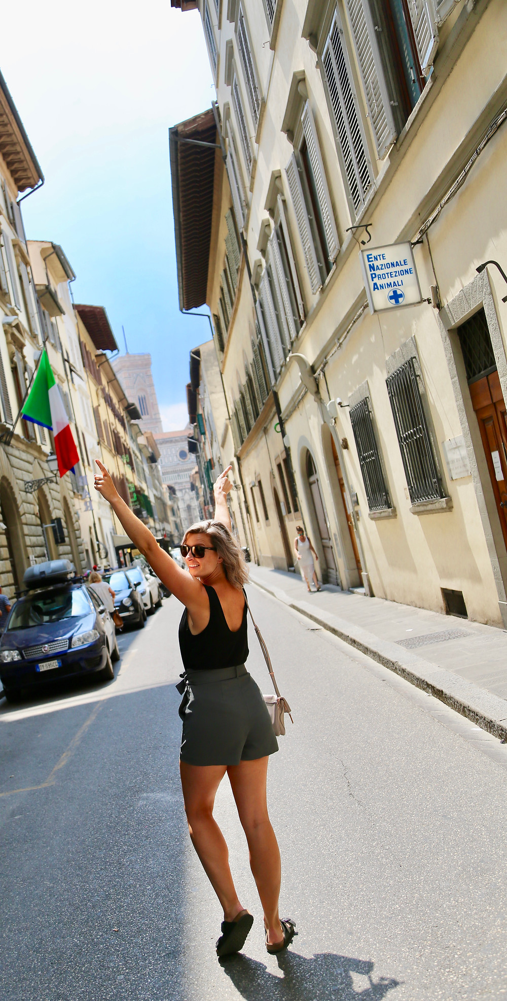 woman arms raised and looking back walking down a street in Rome
