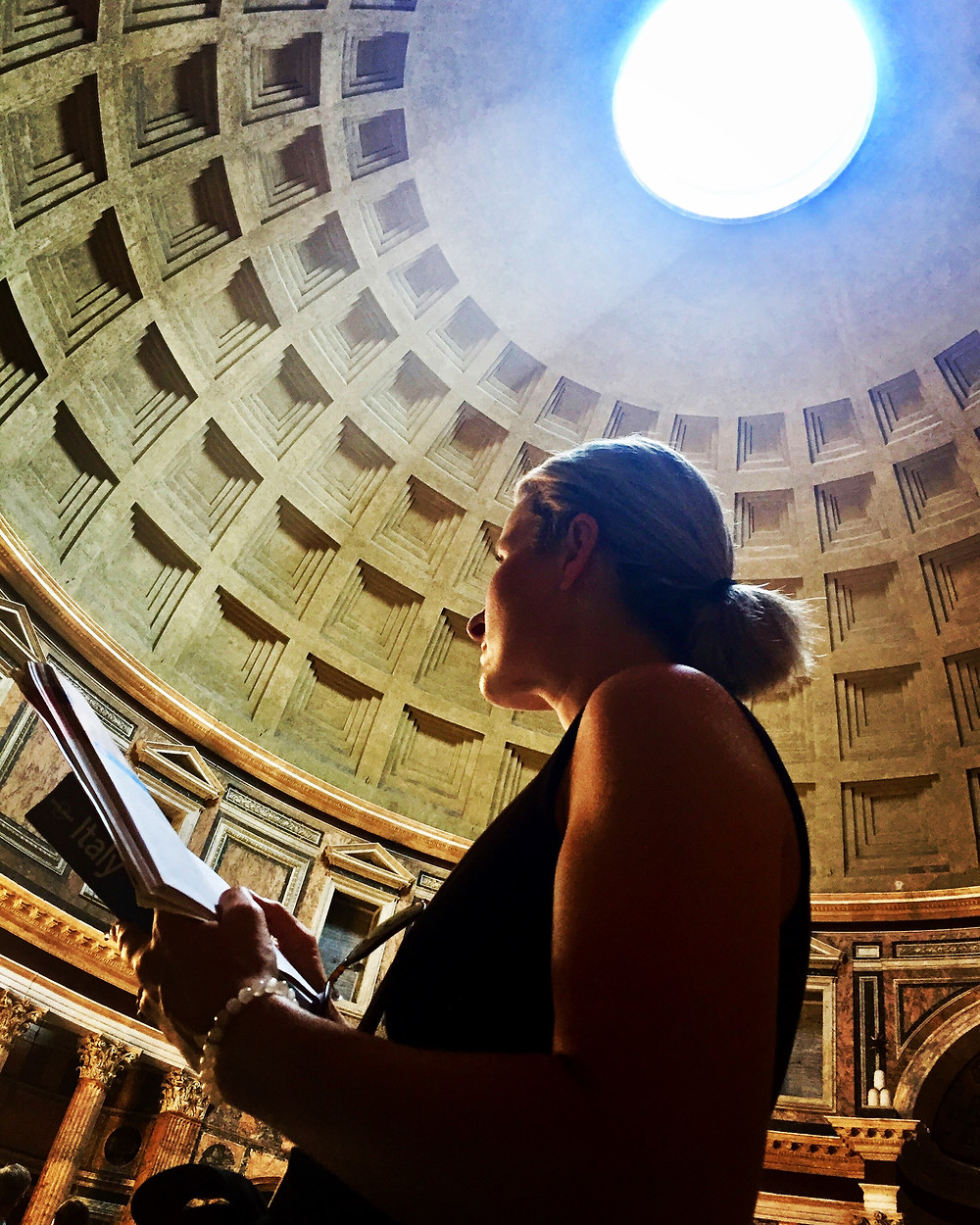 Woman silhouetted reading Lonely Planet guide inside the Pantheon in Rome