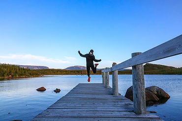 woman facing away jumping excitedly at the end of the pier in Gros Morne National Park