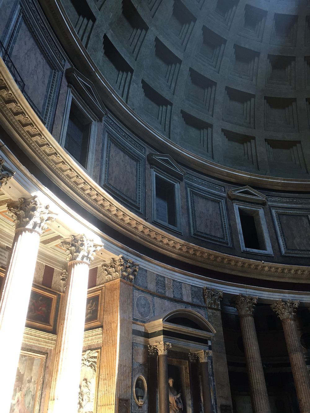 Inside of the Pantheon light streaming in and illuminating inside