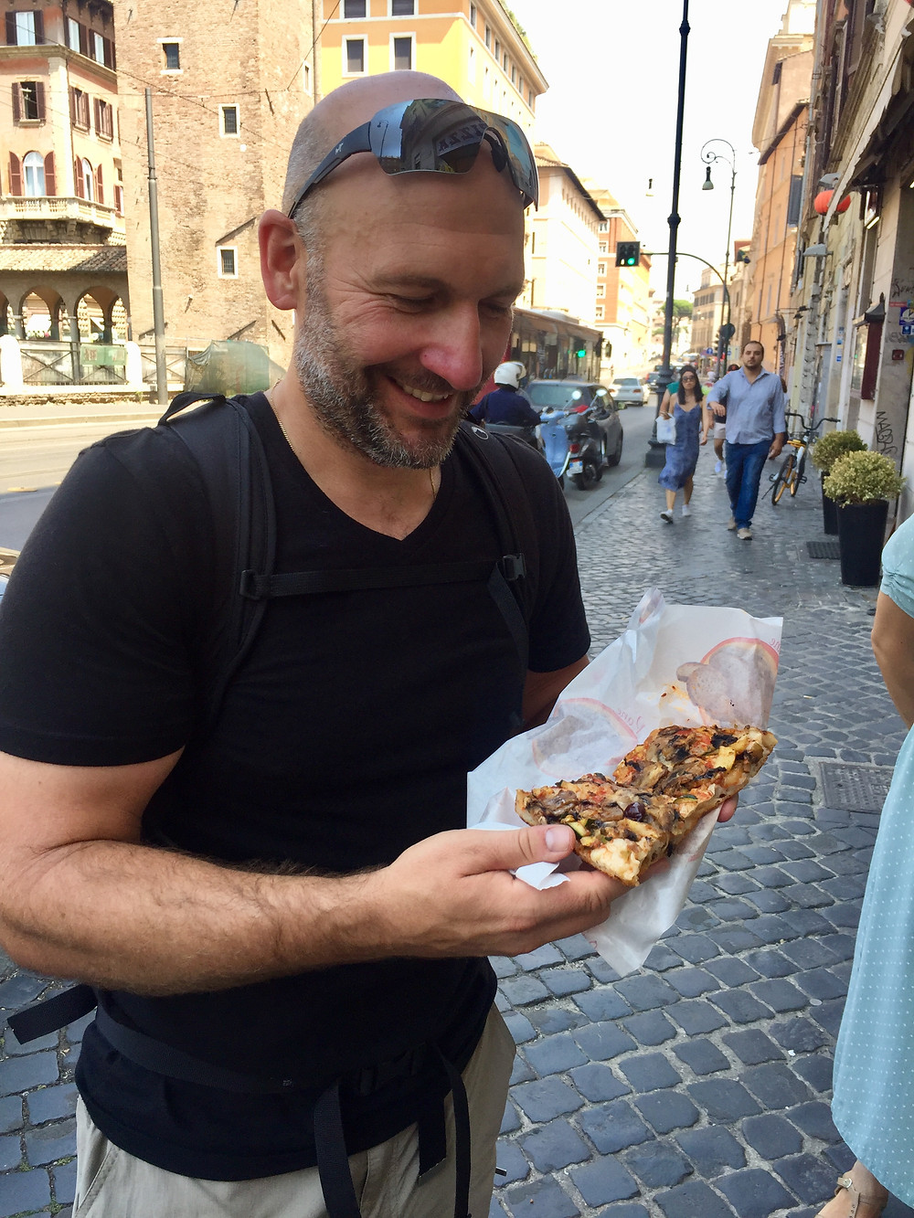 Man smiles ready to eat slice of pizza on a Rome street