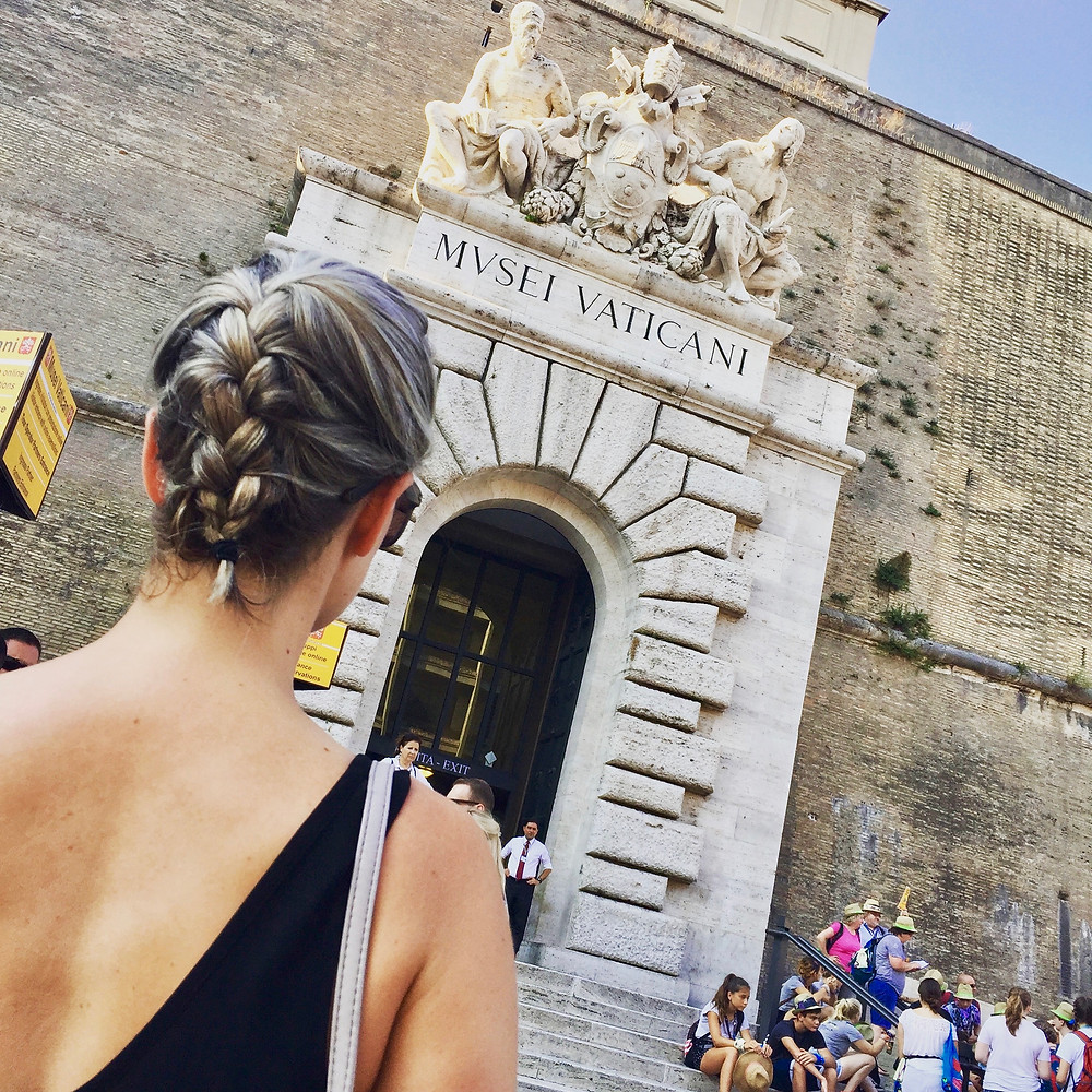 Woman looking at the entrance of the Vatican Museum from the outside