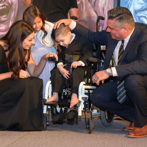 Family on stage with a special needs child at UCP-OC's Life Without Limits Gala