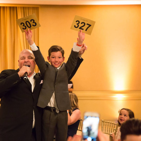 Phot of a child holding up auction numbers, and auctioneer speaking into microphone at UCP-OC's Life Without Limits Gala