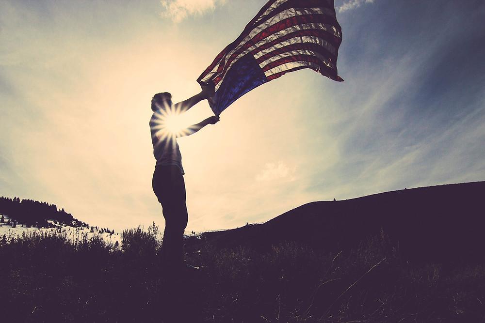 Man Waving American Flag in Dim Sunlight