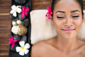 Serene beautiful spa woman relaxing on massage desk .jpg