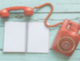 vintage orange-red telephone, notebook o