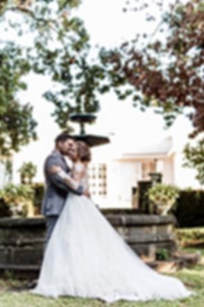 Photograhe. Mariés enlacés près d'une fontaine à La Réunion. Mariage