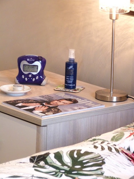 photo shows a bedside table which has an alarm clock, pillow spray, lamp and magazine on it