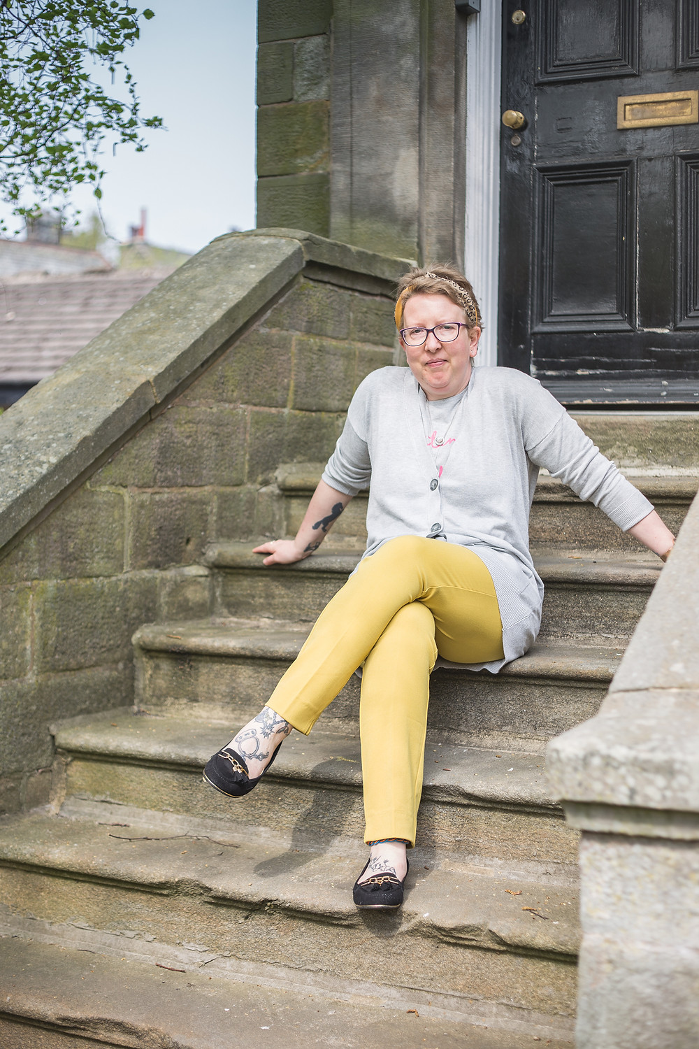 Sarah is sitting on some steps with her legs crossed and her arms behind her. She is wearing yellow trousers, grey cardigan, grey jumper and a silver necklace.