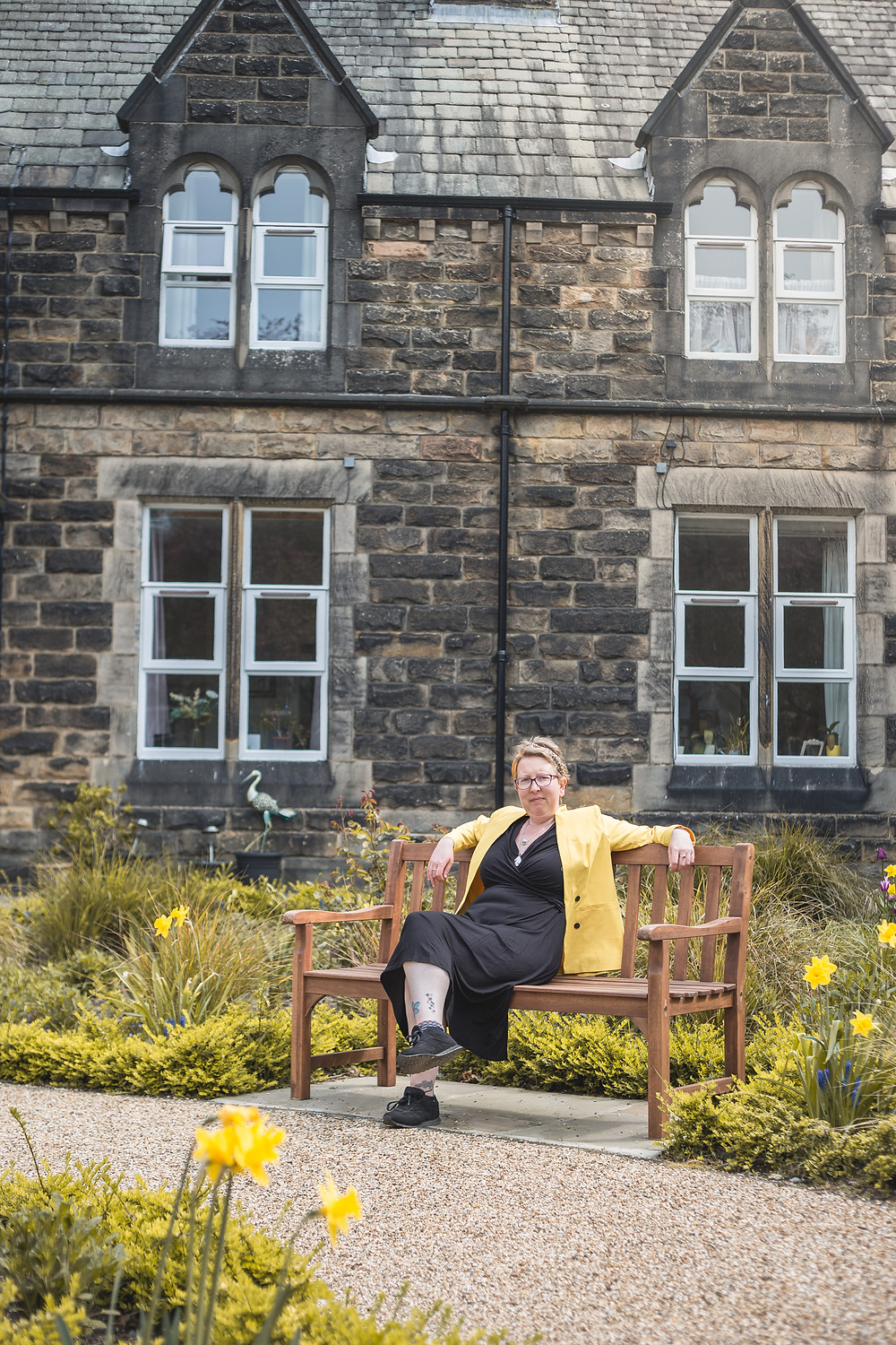 Sarah is sitting on a bench, wearing a black dress, black trainers and a yellow blazer. Behind her you can see arms houses as well as flowers