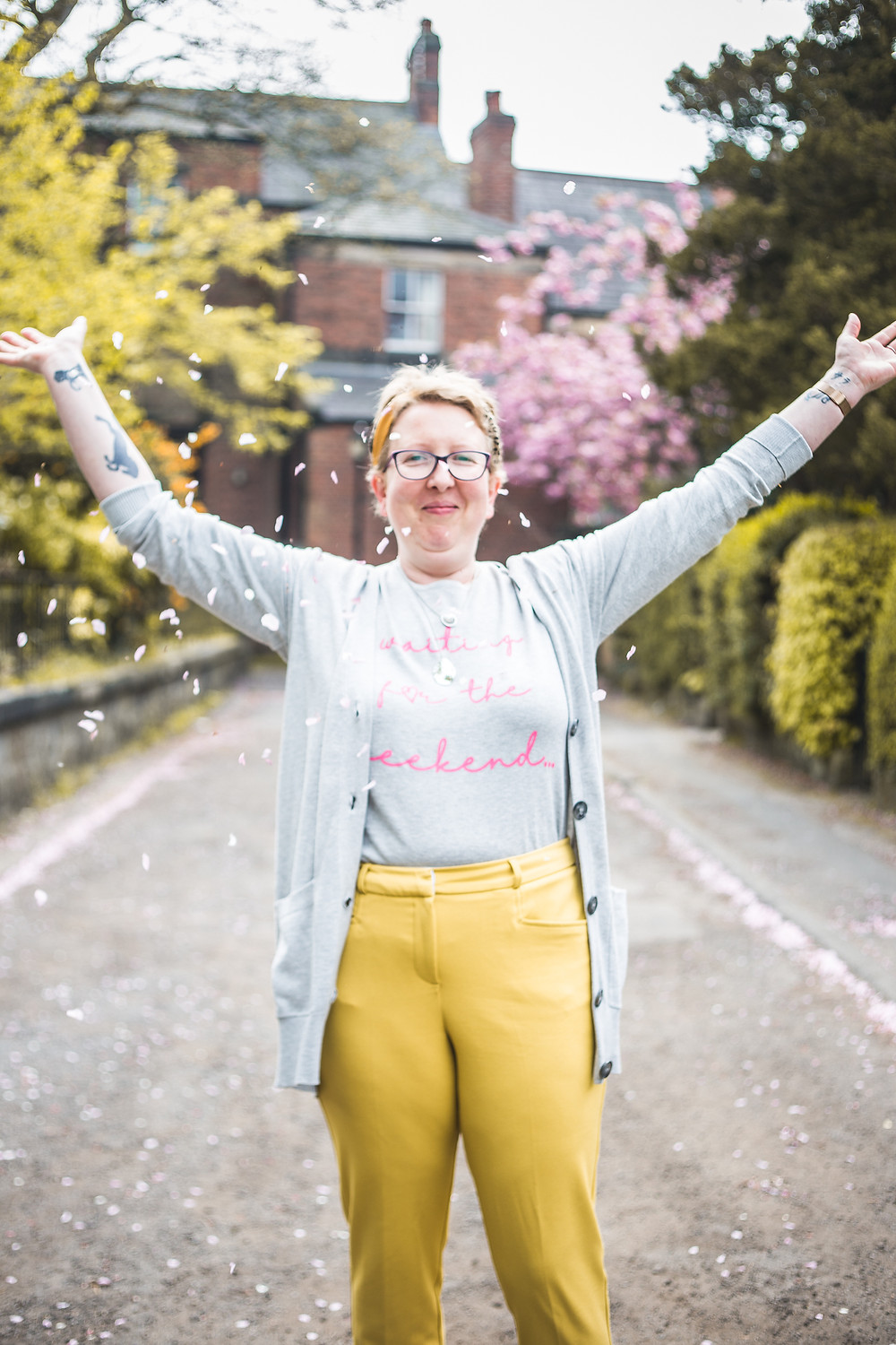 Sarah is facing the camera, smiling, with her arms wide open. She has thrown blossom confetti towards the camera. She is wearing yellow trousers, a thin grey jumper with pink writing on it and a grey cardigan over the top.
