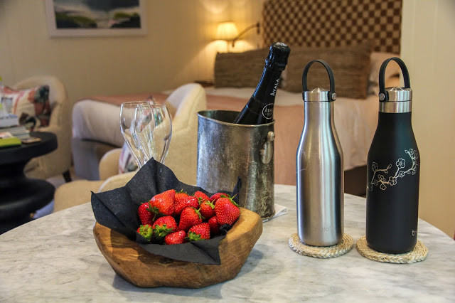 Ohelo reusable water bottles on a table with strawberries and champagne