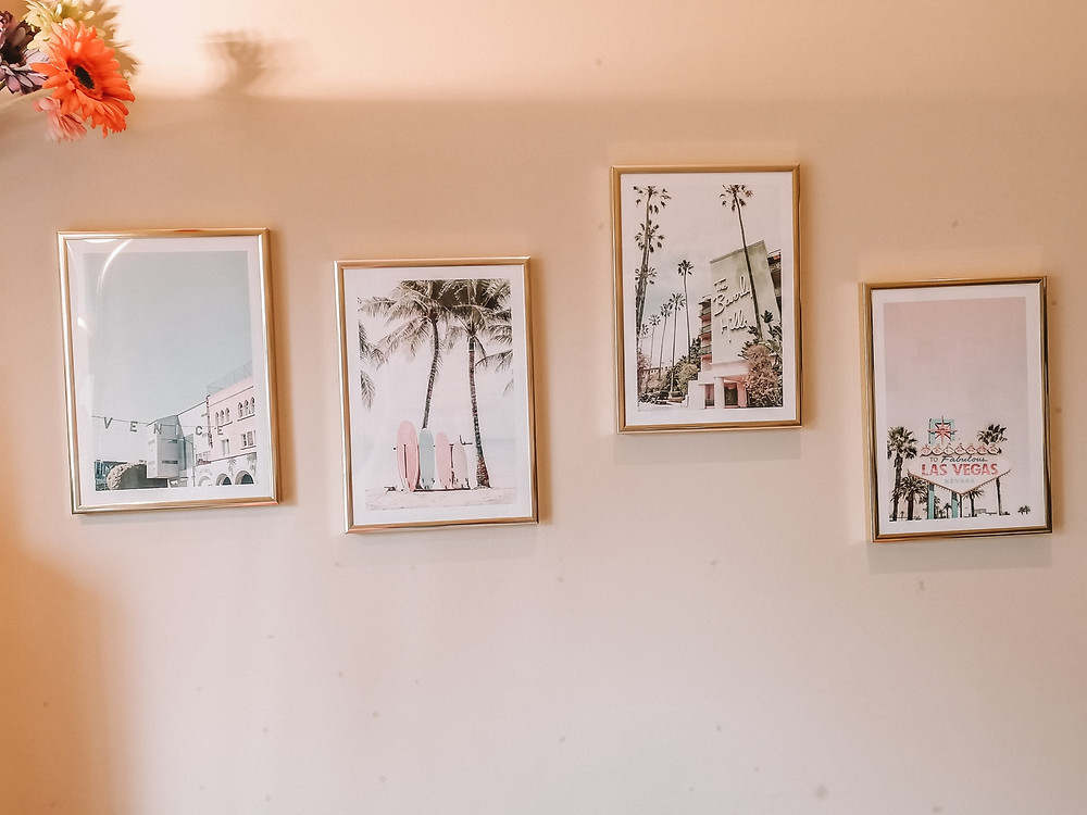 photo shows a gallery wall of posterse on a wall in gold frames
