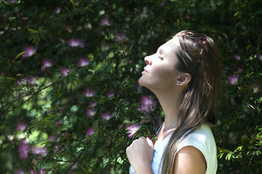woman in a white top standing in front of a green hedge with purple flowers
