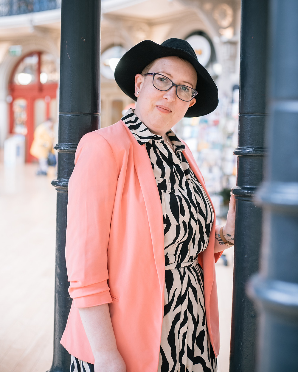 Sarah is wearing a zebra print dress, coral blazer and black fedora hat. she is leaning against a black pole