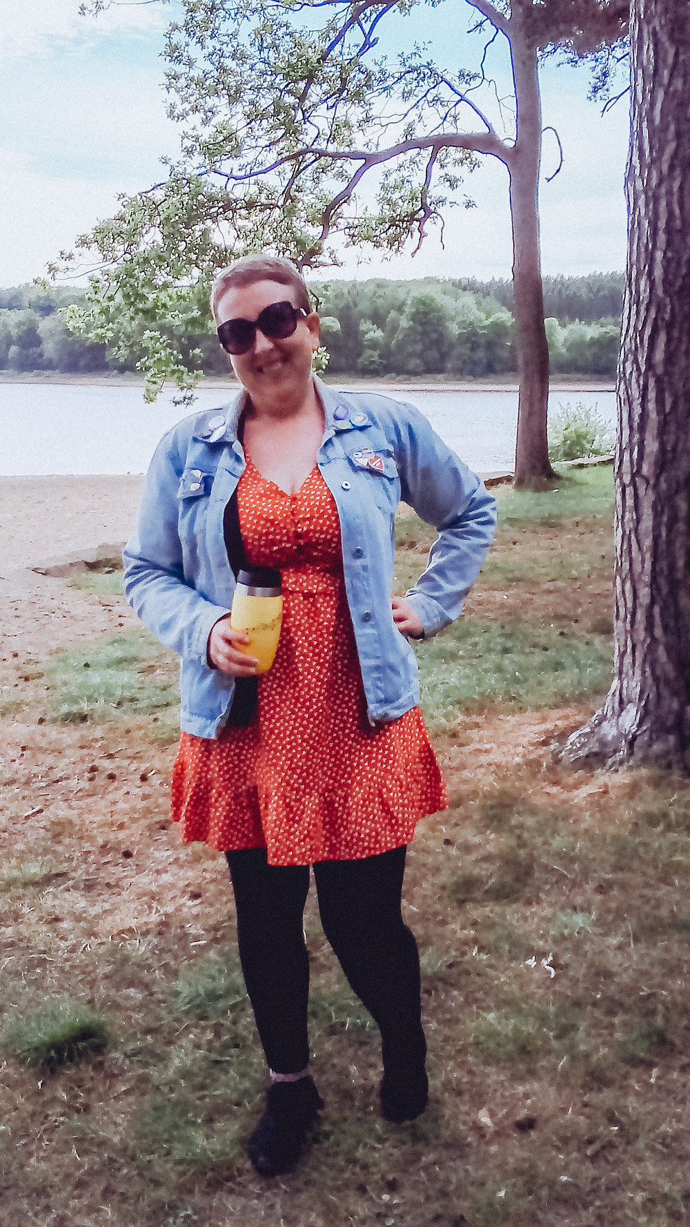 sarah standing on a grassy bank with a lake behind her holding a ohelo reusable coffee cup in one hand whilst the other in on her hip, she is smiling at the camera and is wearing sunglasses, a denim jacket and a red dress with black leggings and trainers.