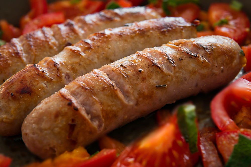 3 sausages on a bed of roasted tomatoes and peppers