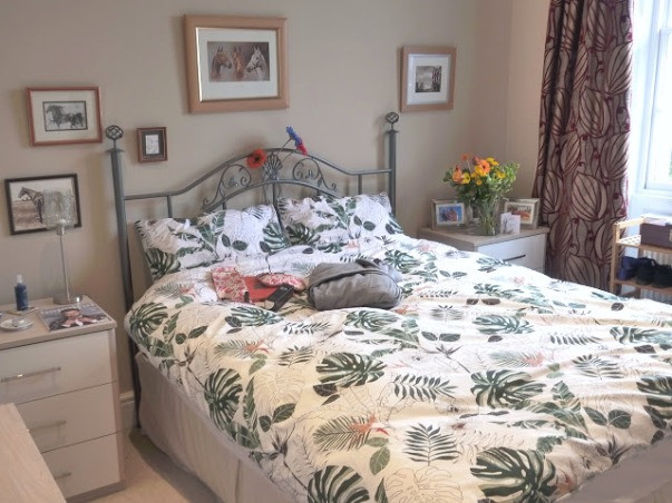 overview of a bedroom the bed linen has a plant theme and there is a grey dressing gown on the bed along with a pink flamingo eye mask.
