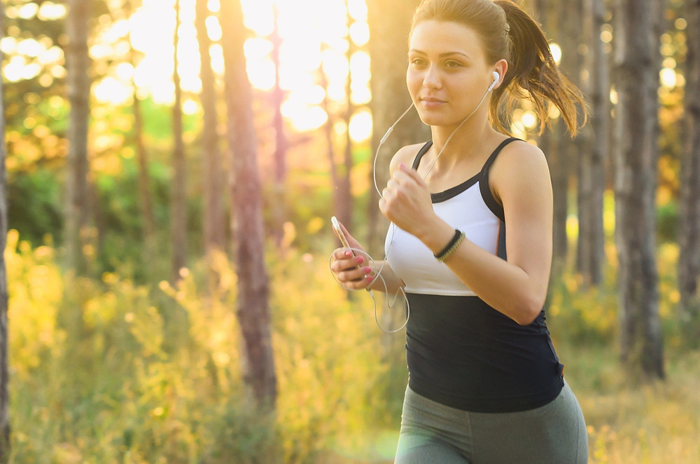 Woman running in thr woods she is wearing earphones and holding a phone