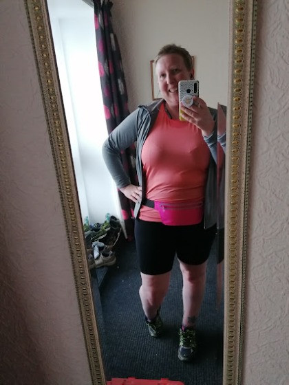 Sarah is stood in front of the mirror and is dressed for running. She is wearing black shorts, a pink waist belt, a grey jacket and a pink top.