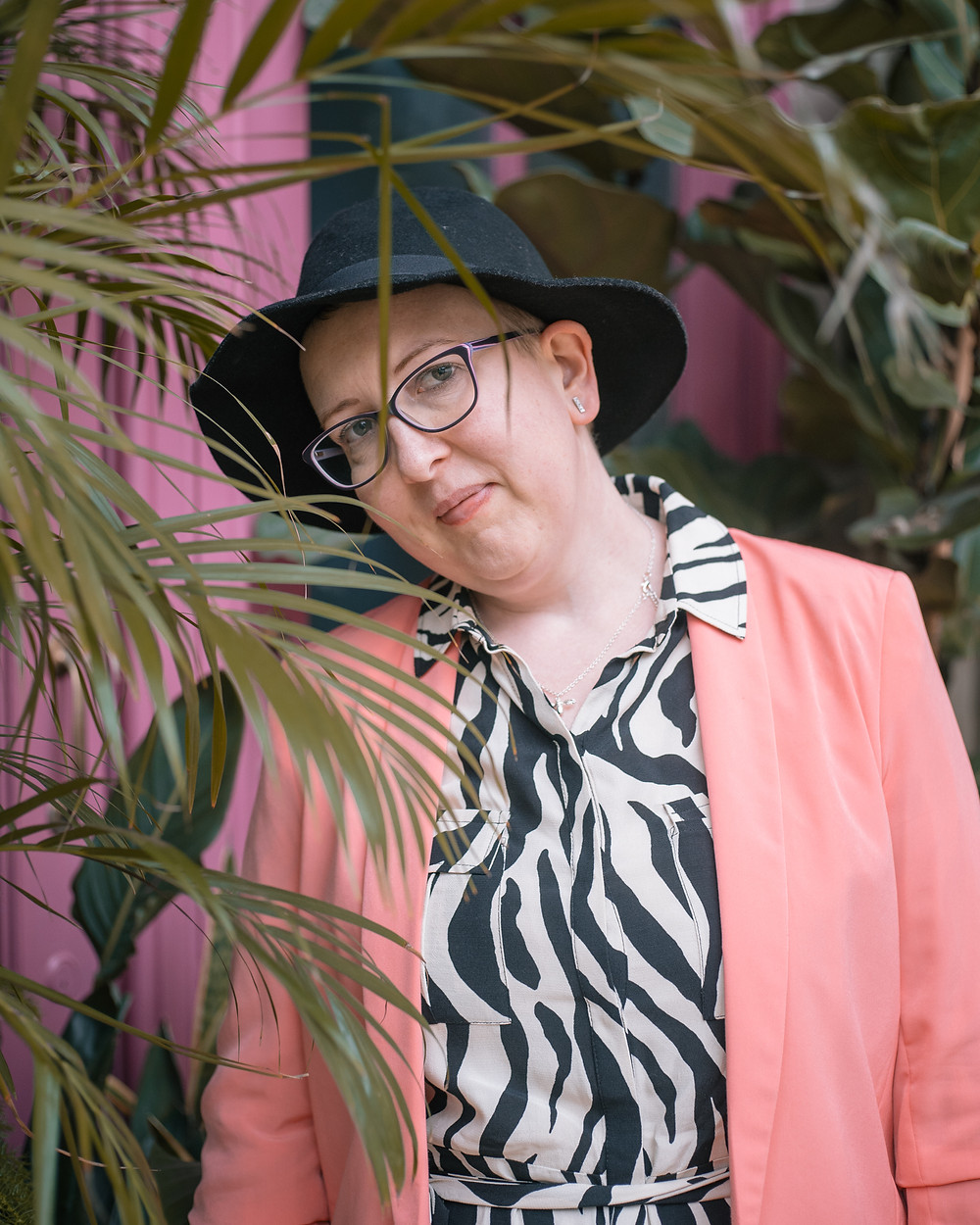 Sarah is hidden behind a plant, you can see her and she is wearing a zebra print dress, black fedora hat and a coral blazer