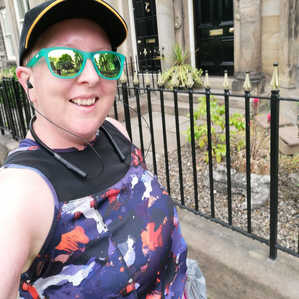 Sarah is looking towards the camera, she is dressed for running and you can see her black, blue and red top, black hat and green sunglasses.