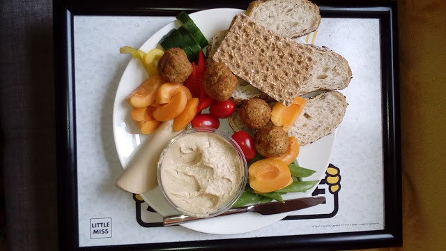 photo shows a plateful of foods on a tray which includes bread, hummus, apricots, tomatoes, ryvita, peppers and vegan ham.