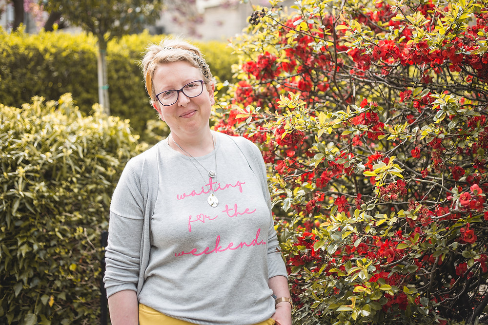 Sarah is standing next to a red flowery bush, she is smiling and she is wearing a grey jumper with pink writing, a grey cardigan and yellow trousers. She is smiling towards the camera.