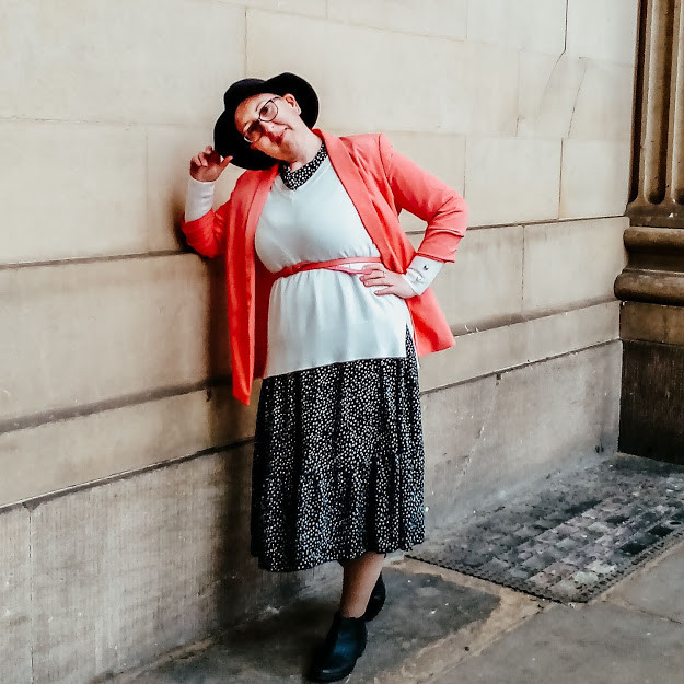 Sarah wearing a black and white spotty dress, with a white jumper over the top, also a coral belt and blazer with black boots and a black fedora hat. She is leaning against a wall with one hand on her hip