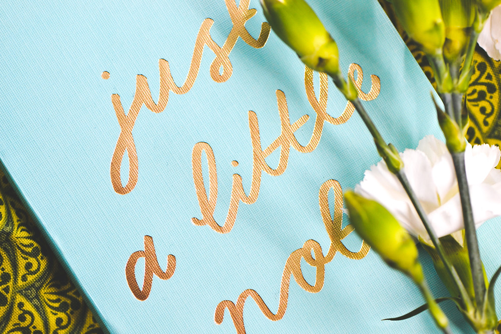 White flowers over a blue canvas with the message 'just a little note' in gold writing