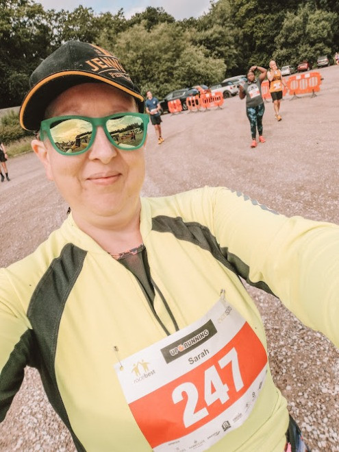 Sarah is looking towards the camera she is dressed for running and has a number attached to her high viz top. She is wearing a black hat and green sunglasses