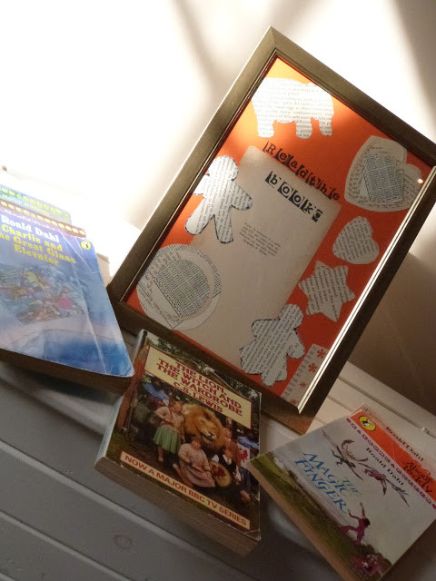 frame with cut out pages of a book in different shapes with books in front