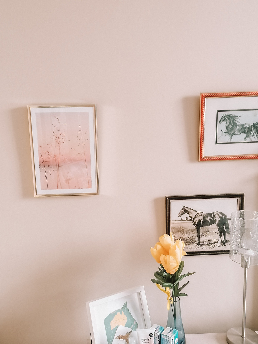 photo shows a wall with an orange sunset picture in a frame