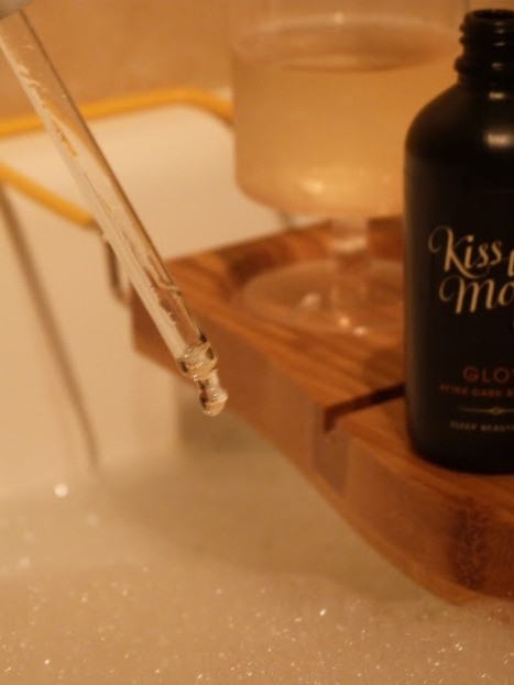 close up view of the bath oil dropper in the background you can see the bottle and a glass of wine sitting on top of the bath board