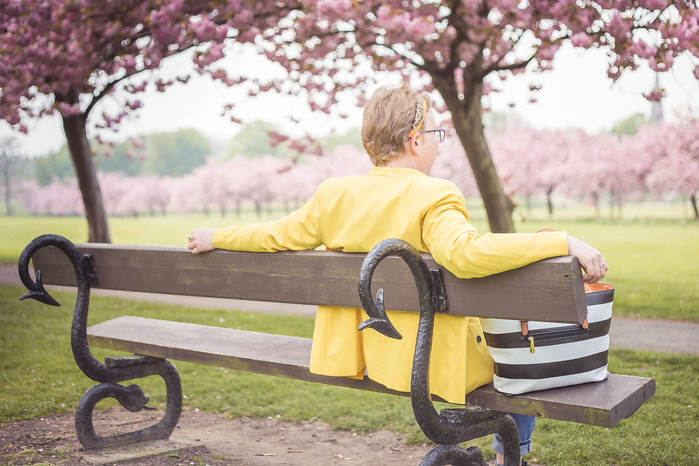 Sarah sitting on a bench looking at pink blossoms she is wearing a yellow blazer you can see a stripey bag she has by her side