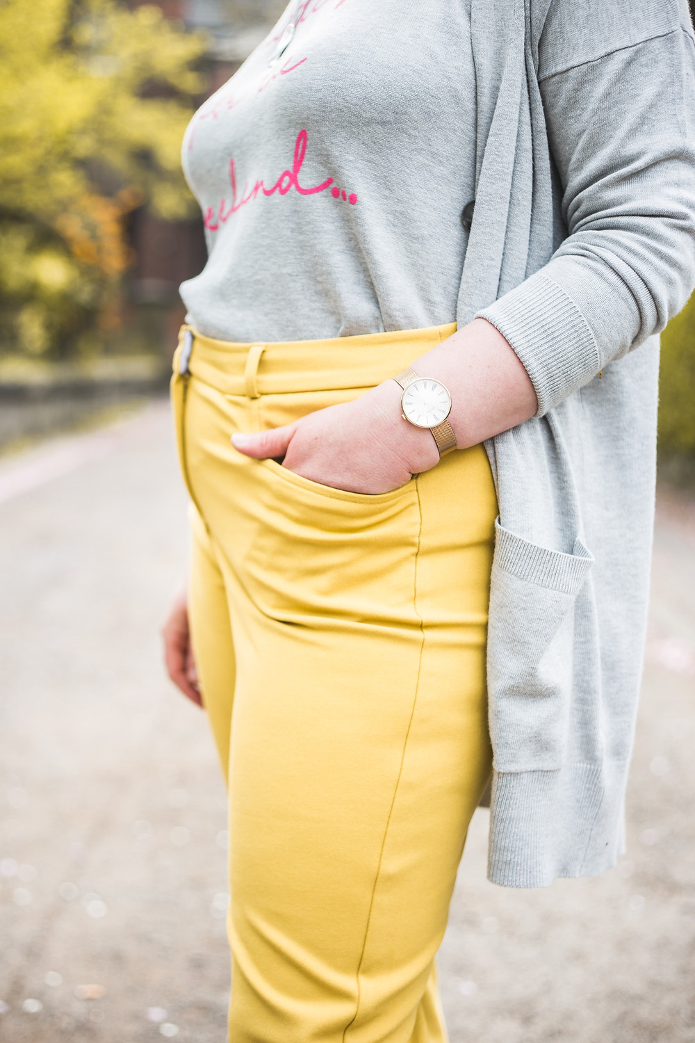 Sarah is wearing yellow trousers, grey jumper with pink writing, grey cardigan and you can see the watch on her wrist and her hand is in her pocket. It is a side shot and you can't see her face.