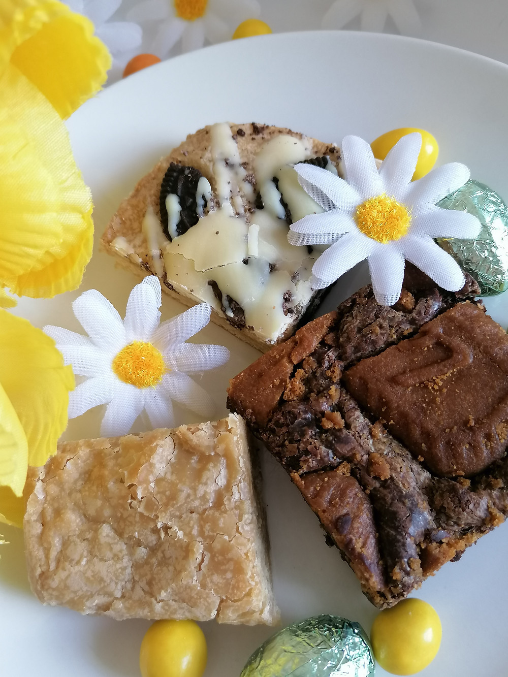 Ditto Bakes brownies and blondies on a white plate with yellow daises